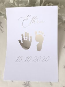 Card printed with foil hand and foot prints with name and date