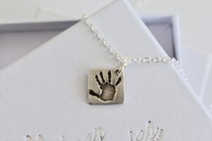 square silver pendant on a chain. The pendant is engraved with a handprint