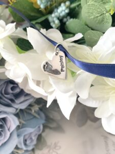 Heart shaped silver pendant on a blue ribbon. The pendant is engraved and personalised with a footprint and text
