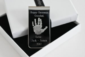 personalised, engraved money clip with a hand print and date and message engraved on it. personalised gift