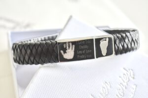 leather bracelet with an engraved clast with hand print and foot print