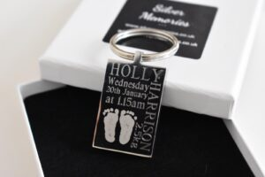 Black rectangular keyring keychain with foot prints engraved into it as well as text