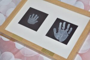 A framed picture with engraved hand and foot prints on stainless steel