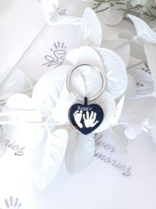 heart shaped pendant keepsake jewelery item with hand and footprints engraved on it