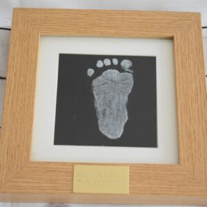 A framed picture of a stainless steel plate engraved with a footprint. Personalised product