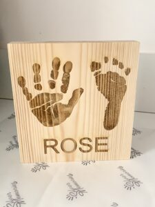 A wooden block engraved with a handprint and a footprint and the name, Rose. Personalised gift