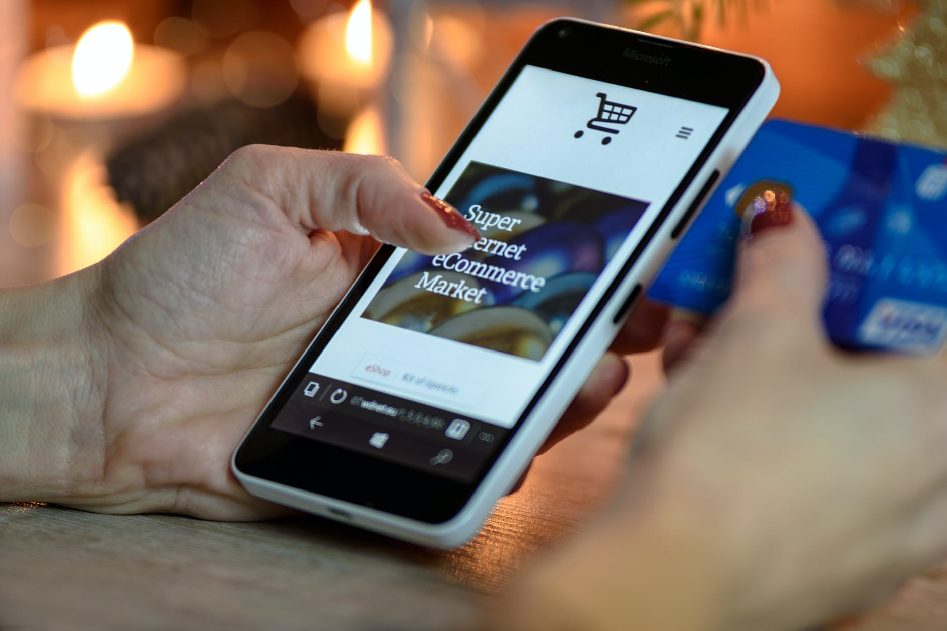 person using black and white smartphone and holding blue card shopping online for personalised handcrafted jewellery
